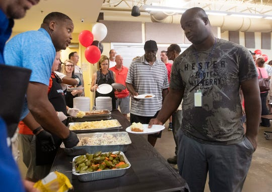 Volunteers serve lunch Friday to clients of the Waterfront Rescue Mission, which celebrated its 70th anniversary.