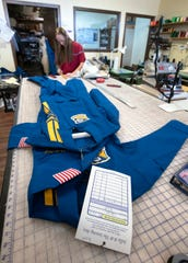 Diane Walter, a seamstress at Jellie B The Sewing Box, works on a Blue Angels flight suit on Thursday.
