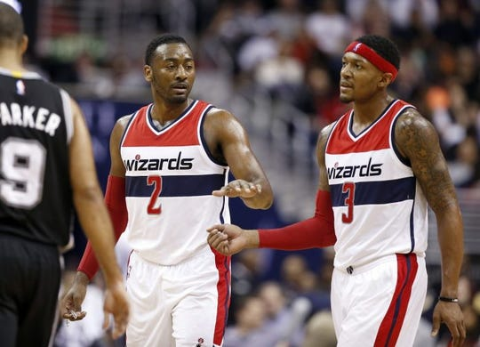 Washington Wizards guards John Wall (2) and Bradley Beal (3) react in the second half of an NBA basketball game against the San Antonio Spurs, Wednesday, Nov. 4, 2015, in Washington. The Wizards won 102-99.