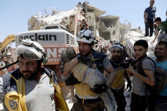 Un miembro de la Fuerza de Defensa Civil Siria conocidos como los 'Cascos Blancos' carga a una niña herida por los ataques aéreos.