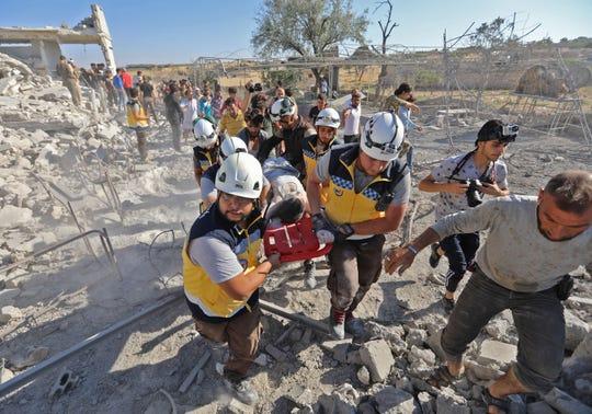 Elementos de los cuerpos de emergencia ayudan a trasladar a los heridos por los bombardeos a las ambulancias.