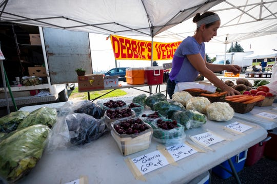 Chrissy Rotarius works at Debbie's Veggies Friday, July 26, 2019, at the Marysville farmer's market. Rotarius said they were late in planting their sweet corn this year due to weather, but should have it soon.