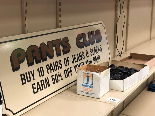 """An old sign for the """"Pants Club"""" sits on shelves behind the counter at Kleffel's in Hanover. Employees would track purchases on index cards that were stored in boxes at the store — several of which were saved after a fire damaged the original building in 1990.  Today, as the store prepares to close, customers can redeem their pants cards for points toward a prize giveaway Sept. 7."""