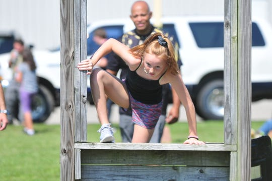 Rylee McClain climbs through a window obstacle Friday, July 26, 2019, under the watchful eye of Officer Tim Davis during Richmond Police Department's Youth Police Academy.