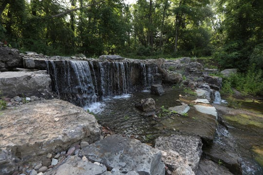 A waterfall with an on and off switch was built on a part of the property close to both the gravel road and a walking trail.