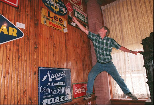 1996: Harry Hanford of Victor takes down a sign at the Spaghetti Warehouse auction. He bought five signs for about $50 each