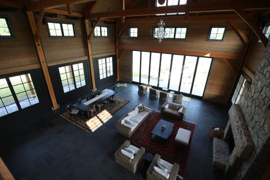 A view of the first floor area that has a dining room table, living room area and fireplace.   The dark panels with windows work like garage doors that can raise and lower.