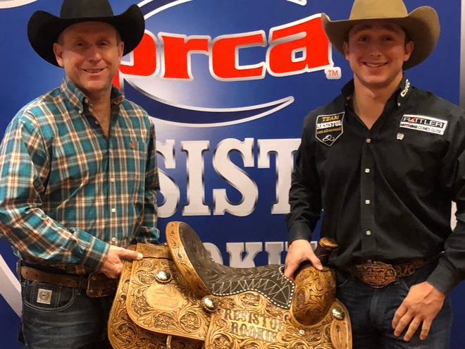 San Angelo's Ty Harris, right, shows his Resistol Tie-Down Roping Rookie of the Year saddle with his father Walt Harris, left.