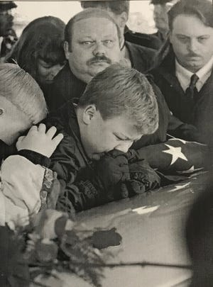 Jimmy McBride, brother of murdered soldier Pvt. Tracie McBride, leans on her coffin at Fort Snelling National Cemetery in St. Paul, Minnesota, on March 8, 1995. Jim McBride watches the crowd behind his son.