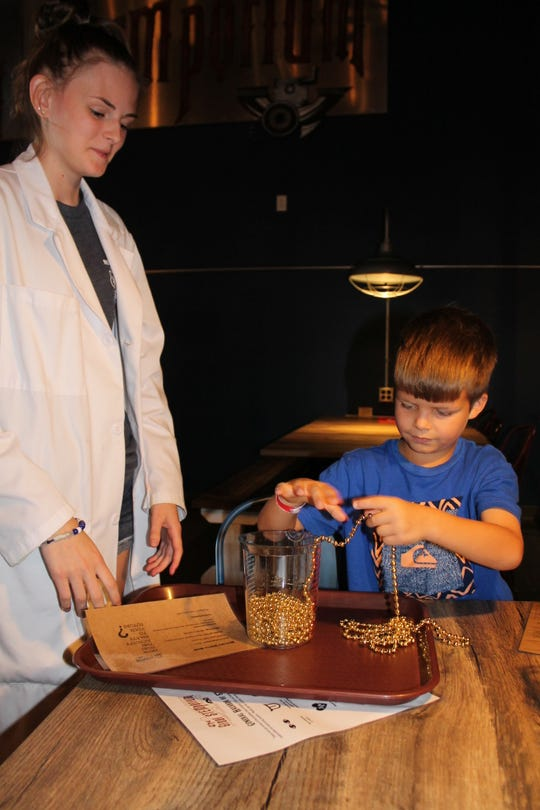 Ciera Barnett, junior lab assistant, and Marshall Sheetz try out the inertia beads at the STEMporium in Lewes.