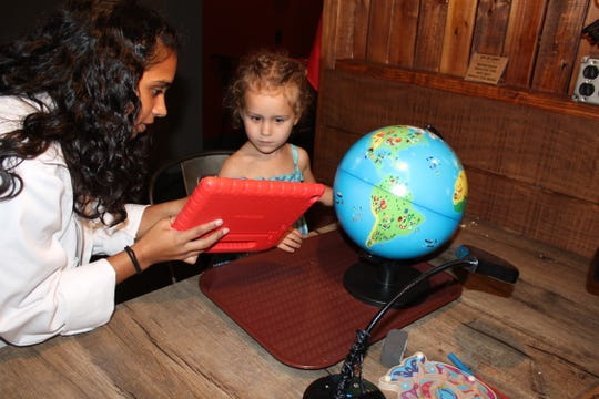 Puja Jani, junior lab assistant, shows Madelyn Donald, 3, how to work the interactive globe.