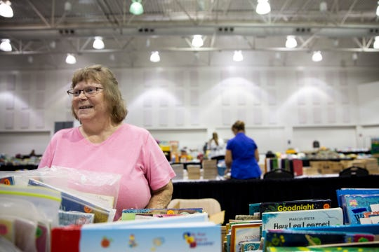Julie Jeffries of Pierre, S.D., sells school supplies that she accumulated during her teaching career, Friday, July 26, at the Sioux Falls Convention Center. Jeffries taught for around 30 years and estimates that she gathered over 2,000 books during her career.