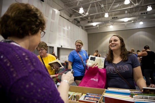 Kayla Rye searches for books for her fifth grade classroom at the swap, Friday, July 26, at the Sioux Falls Convention Center.