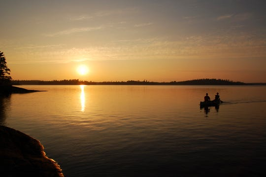 The sun sets as two paddlers make their way across Lac La Croix in this file photo taken in the Boundary Waters Canoe Area Wilderness near Ely.