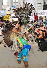 In this Dec. 2, 2017, photo, a supporter of the Bears Ears and Grand Staircase-Escalante National Monuments wears a colorful headdress during a rally against President Trump's reduction of the two National Monuments in Salt Lake City.