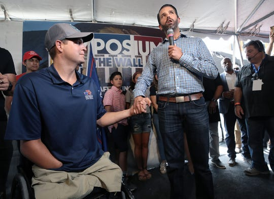 "Donald Trump Jr. stops by the ""Symposium at the Wall: Cartels, Trafficking and Asylum,"" hosted by WeBuildTheWall founder Brian Kolfage, left, Friday, July 26, 2019, in Sunland Park, New Mexico. The symposium, which was streamed live on the internet, seeks to tell the public of the need for a border wall."