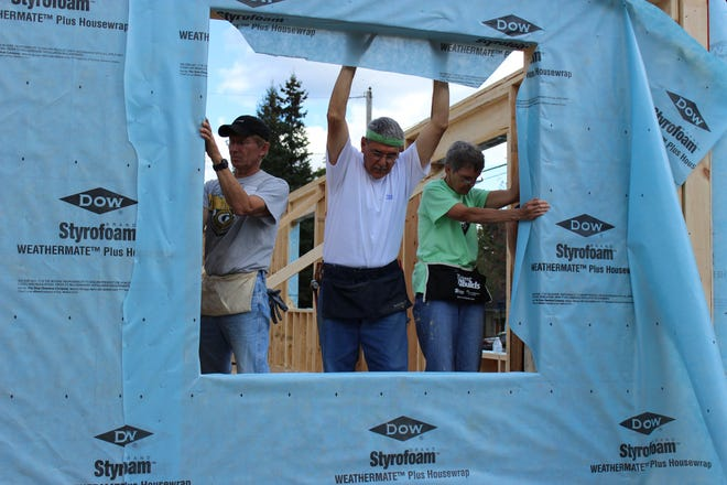 Lou Santangelo (middle) and Lynne Santangelo (right) work with another Habitat for Humanity volunteer to help build a house.