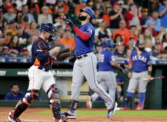 Texas Rangers' Nomar Mazara, front right, points up as he crosses the plate past Houston Astros catcher Max Stassi, left, after his home run during the sixth inning of a baseball game Sunday, July 21, 2019, in Houston. (AP Photo/Michael Wyke)