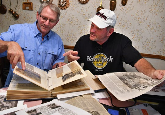 Jim Davis, left, and Stephen Davis look through newspaper clippings and photos of their father, Truman Davis, who was a Korean War POW for 32 months. Truman Davis died Tuesday, July 23 at the age of 90.
