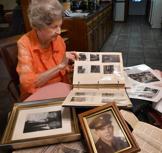 Anna Lee Davis, wife of the late Truman Davis, looks through a photo album of her husband's military service, including his time as a prisoner of war during the Korean War.