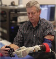 Keven Walgamott uses the LUKE arm to pick grapes. Photo courtesy of the University of Utah Center for Neural Interfaces.