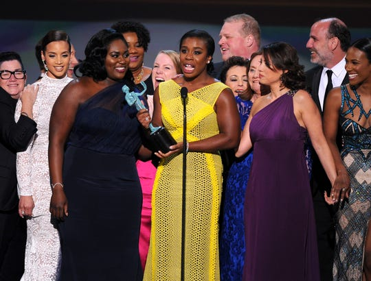 "Uzo Aduba, center, and the cast of ""Orange is the New Black"" accept the award for outstanding performance by an ensemble in a comedy series at the Screen Actors Guild awards in 2015."