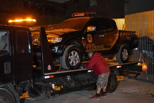 A fake police car that was used in robbery is loaded onto a flat-bed truck in the outskirts of Sao Paulo, Brazil, Thursday, July 25, 2019. Authorities at Sao Paulo's Guarulhos International Airport say eight armed men raided a terminal and escaped with some 1,600 pounds of precious metals, including gold.