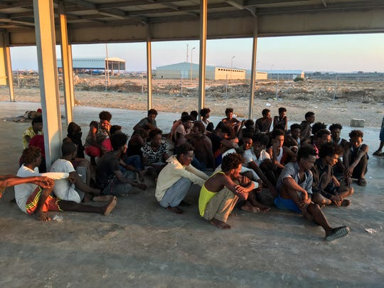 Rescued migrants sit on a coast some 100 kilometers (60 miles) east of Tripoli, Libya, Thursday, July 25, 2019.