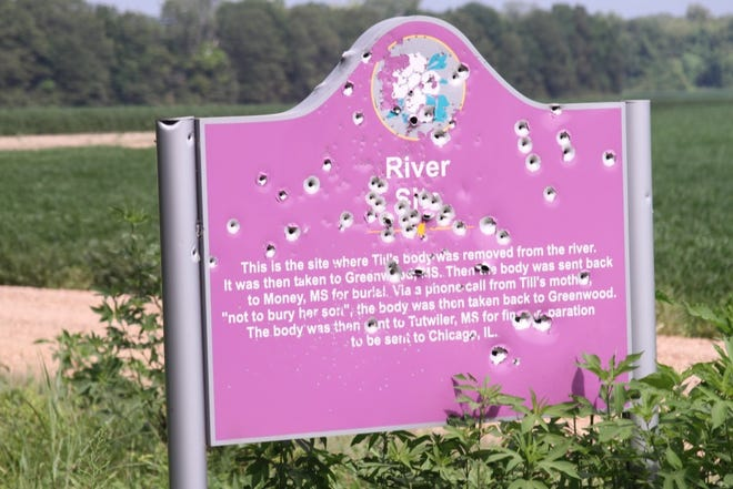 Bullet holes cover the sign that marks the location where Emmett Till's body was discovered in the Tallahatchie River.