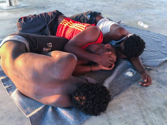 Rescued migrants rest on a coast some 100 kilometers (60 miles) east of Tripoli, Libya, Thursday, July 25, 2019.