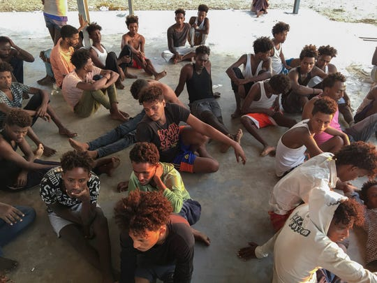 Rescued migrants sit on a coast some 100 kilometers (60 miles) east of Tripoli, Libya, Thursday, July 25, 2019. The U.N. refugee agency and the International Rescue Committee say up to 150 may have perished at sea off the coast of Libya.