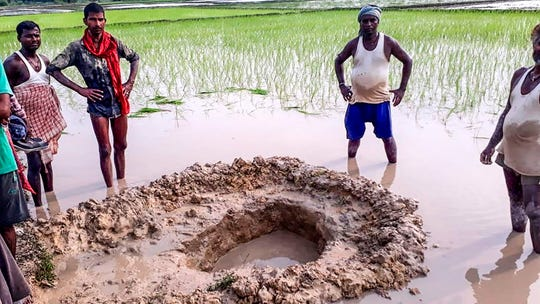 In this photo taken on July 22, 2019, villagers and farmers pose around the crater of a meteorite that crashed in a field at Mahadeva village in Madhubani district of the Indian eastern state of Bihar, before it was brought on July 24 to the Patna Museum.