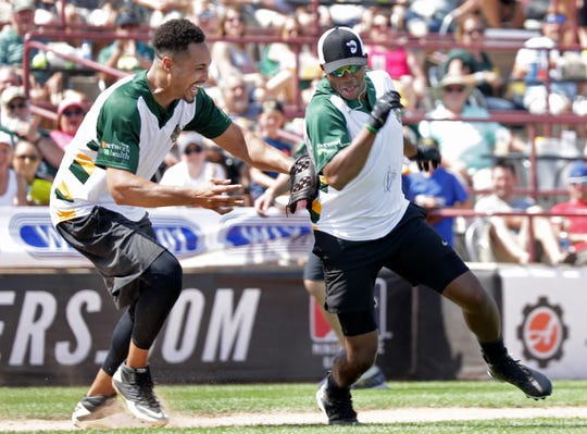 Super Bowl champion and Wisconsin football legend Travis Beckum tags country music star Jimmie Allen during the Donald Driver Charity Softball Game on Saturday at Neuroscience Group Field at Fox Cities Stadium in Grand Chute.