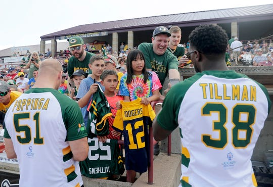 Former Green Bay Packer Brady Poppinga and former Chicago Bear Charles Tillman sign autographs during the Donald Driver Charity Softball Game on Saturday at Neuroscience Group Field at Fox Cities Stadium in Grand Chute.