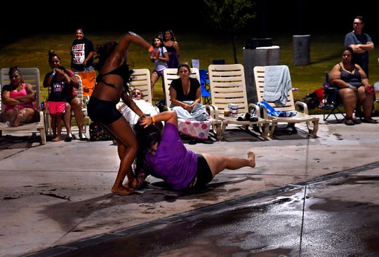 """Two women fight at Adventure Cove during Friday's Dive-In Movie of """"Jaws"""" July 26, 2019. The pair began swinging fists and pulling hair midway through the film, continuing for several minutes while pool personnel and others tried to separate them."""