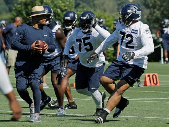 Seattle Seahawks defensive tackles Earl Mitchell (75) and Al Woods (72) work with defensive coordinator Ken Norton Jr., left, during NFL football training camp, Thursday, July 25, 2019, in Renton, Wash.