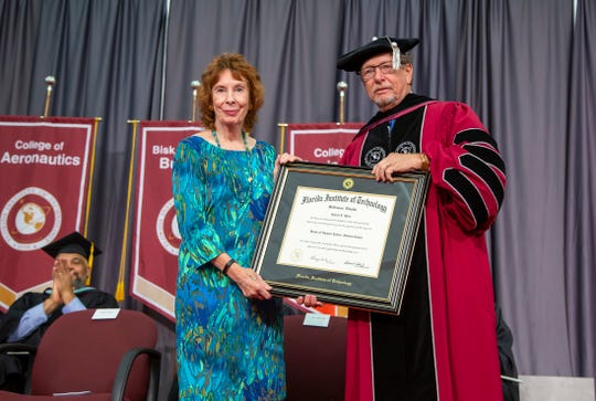 "Jenifer Marx accepts an honorary degree on behalf of her late husband, Sir Robert Marx, at Florida Tech's summer commencement ceremony on Saturday, July 27. ""Bob"" Marx died July 4 at the couple's Indialantic home at age 82."