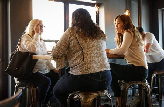 Patricia Liu, right, and Sabrina Bousbar, both members of Joe Biden's campaign team, speak with Diane Ward of Iowa City at a coffee shop on Friday, July 19, 2019, in Iowa City.