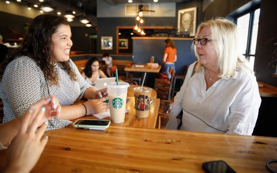 Sabrina Bousbar, a member of Joe Biden's campaign team, speaks with Diane Ward of Iowa City at a coffee shop on Friday, July 19, 2019, in Iowa City.
