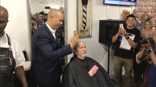Cory Booker shaves the head of campaign volunteer John Kaiser of Des Moines at Platinum Signature Barbershop in West Des Moines on Friday, July 26, 2019.
