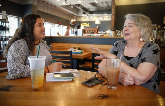 Janet Greazel of Coralville speaks with Sabrina Bousbar, a member of Joe Biden's campaign team, at a coffee shop on Friday, July 19, 2019, in Iowa City.