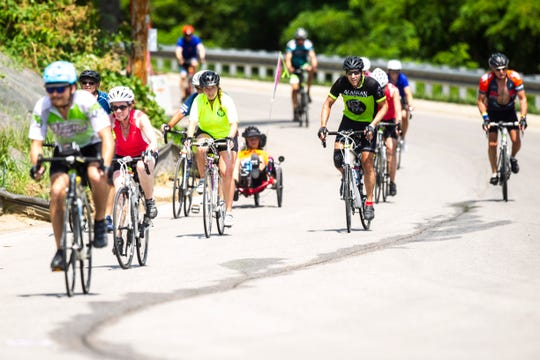 RAGBRAI riders make it to the top of the hill at Rand Park while nearing the finish of the 427 mile route on day seven, Saturday, July 27, 2019, in Keokuk, Iowa.