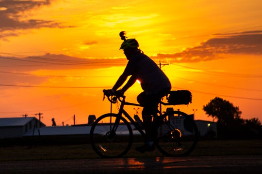 RAGBRAI riders kick off day seven as the sun rises, Saturday, July 27, 2019, outside West Burlington, Iowa.