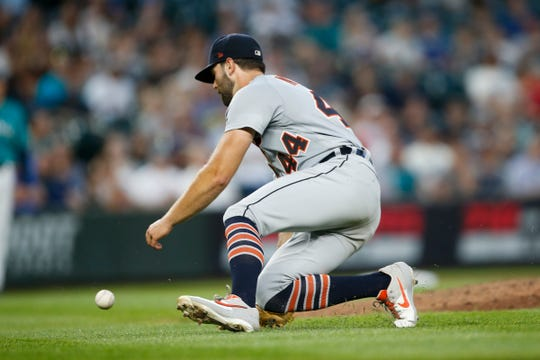 Tigers pitcher Daniel Norris goes to the ground for a ball during the sixth inning of the Tigers' 3-2 loss on Friday, July 26, 2019, in Seattle.