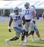 Lions offensive linemen Ryan Pope (74) and Frank Ragnow warm up during practice during training camp on Saturday, July 27, 2019, in Allen Park.