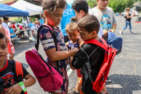 Dayvonna Dillon, 9, of Detroit, helps Melvin Molina, 10, with his sister, Lila Molina,1, after picking out free backpacks at the Samaritan's Feet International and several local partner organizations' event at Cornerstone Church in Wayne, Mich. on Saturday, July 27, 2019.