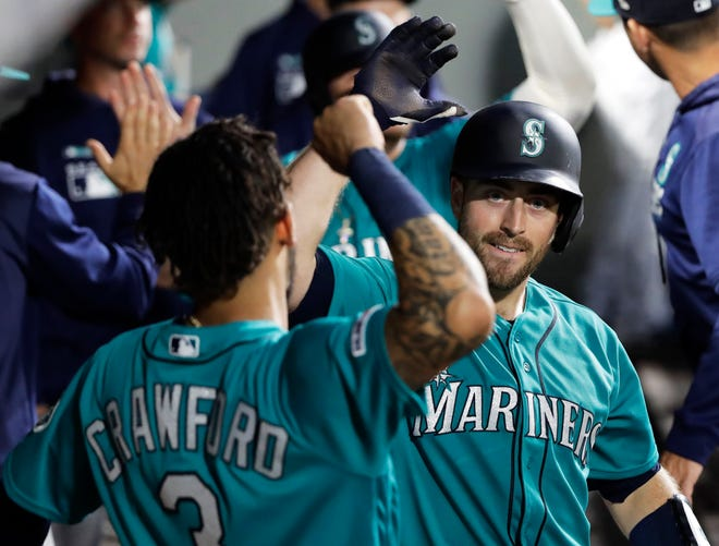 Seattle Mariners' Tom Murphy, right, is greeted by J.P. Crawford, left, after Murphy hit a tying, two-run home run during the seventh inning.
