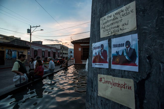 """Posters and signs placed on one of the sculptures outside the Constitutional Court show a cartoon of the Guatemalan President Jimmy Morales with the word """"traitor"""" """"#jimmy turncoat"""" during a press conference organized by civil society groups in Guatemala City, Friday, July 26, 2019. The signs came up after the Trump administration signed an agreement with Guatemala Friday that will restrict asylum applications to the U.S. from Central America."""