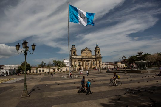 People walk through the central park in Guatemala City, Friday, July 26, 2019. The Trump administration signed an agreement with Guatemala Friday that will restrict asylum applications to the U.S. from Central America.