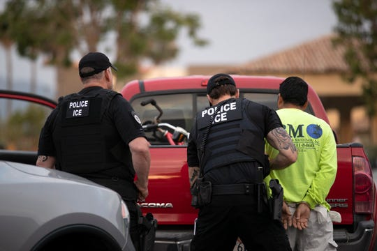 In this July 8, 2019, photo, a U.S. Immigration and Customs Enforcement (ICE) officers detain a man during an operation in Escondido, Calif.